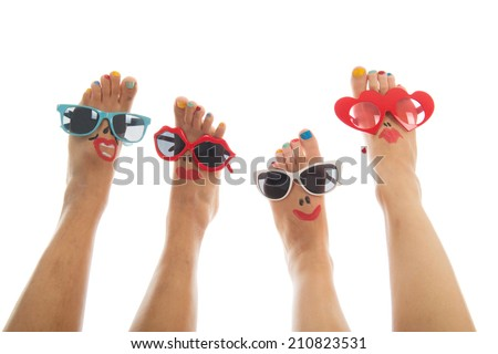 Happy and funny black and caucasian summer feet with colorful nail polish and sunglasses - stock photo