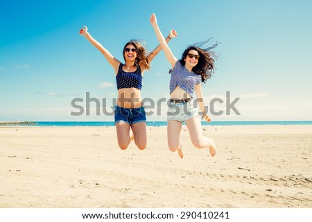 Happy and funny girl friends jumping on the beach, Some blur on legs becacuse of movement - stock photo