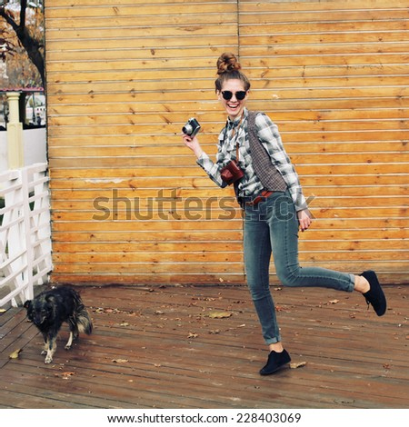 Happy and funny hipster woman with retro camera photographing the dog on the street. Photo toned style Instagram filters. - stock photo