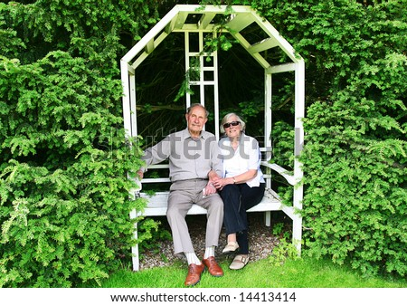 Happy and Healthy active couple at 80 hold hands on Love Seat