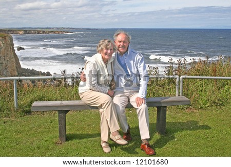 Happy and Healthy at 80 couple enjoy a day out at the English coastline - stock photo