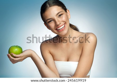 Happy and Healthy, natural organic raw fresh food concept / portrait of attractive smiling girl holding green apple in her hand over blue background  - stock photo
