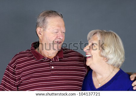 Happy and healthy senior couple laughing together, studio shot over grey background. - stock photo