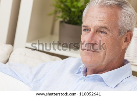 Happy and healthy senior man sitting on a sofa at home thoughtful and happy