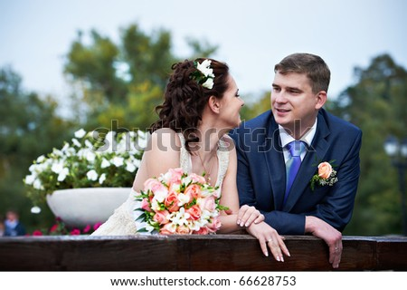 Happy and in love with the bride and groom on wedding walk in park - stock photo