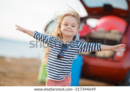 happy and joyful child in car and suitcases background. vacation and car trip concept. freedom and wind. girl traveler - stock photo