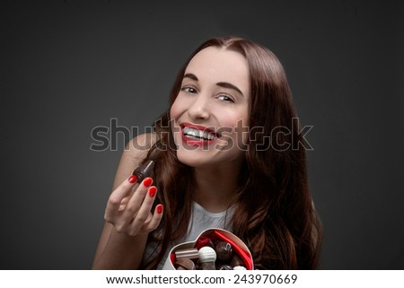 Happy and joyful young woman holding heart box with candies and eating them on grey background. Happy valentines gift concept - stock photo