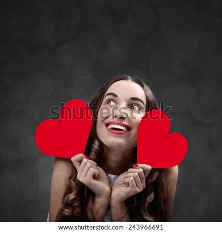 Happy and joyful young woman holding red hearts on grey background in studio. Happy valentines greeting concept - stock photo