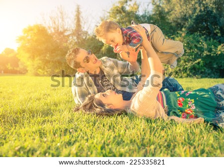 happy and playful parents with kid. Mom holding up his son at the park - stock photo