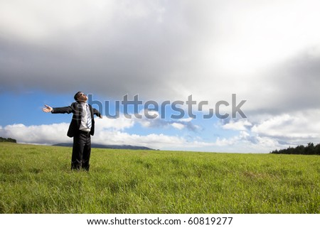 happy and Relaxation businessman standing on the green field enjoy sunlight - stock photo