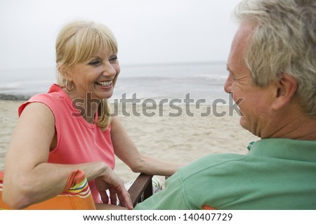 Happy and relaxed middle aged couple sitting on beach - stock photo