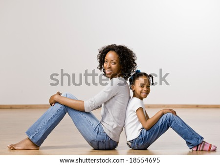 Happy and relaxed mother and daughter sitting back to back - stock photo