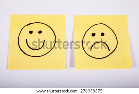 Happy and Sad Faces on Two Pieces of Memo Paper. - stock photo