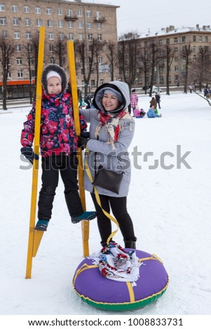 Happy and satisfied mother and child try to walk on stilts at winter. Social activities are at Maslenitsa holiday