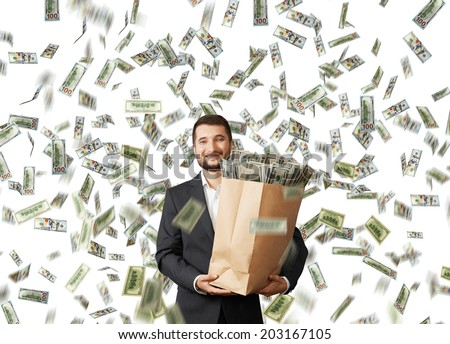 happy and smiley businessman holding paper bag with money under dollar's rain - stock photo