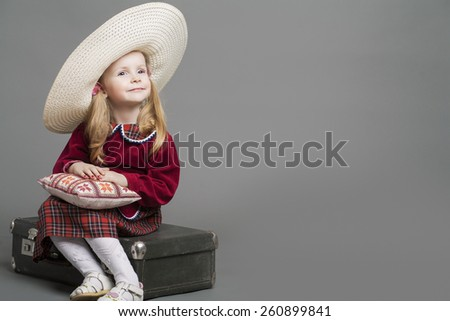 Happy And Smiling Caucasian Child Posing in Big Round Sombrero Hat and Sitting on Outdated Suitcase. Against Gray Background. Horizontal Image - stock photo