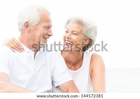 Happy and smiling couple in front of white sky - stock photo