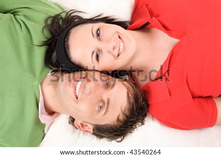Happy and smiling couple lying on the floor - stock photo