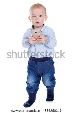 Happy and smiling excited baby boy goes and holding smartphone. Child wants to play. Isolated on white background - stock photo