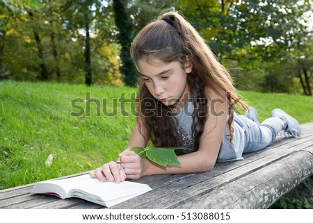 Happy and smiling girl reading book at park