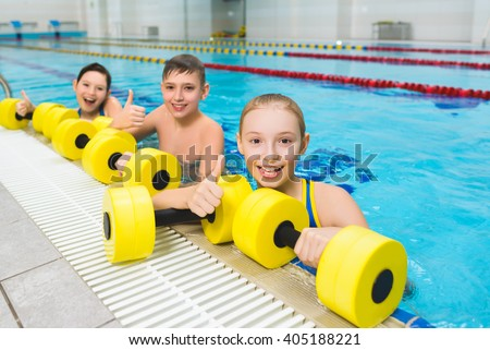 Happy and smiling group of children doing exercises in a swimming pool - stock photo