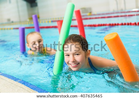 Happy and smiling group of children learning to swim with pool noodle - stock photo