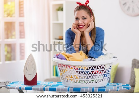 Happy and smiling hostess prepares clothes for ironing at home - stock photo