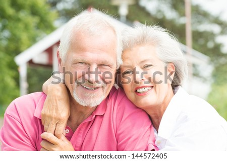 Happy and smiling senior couple at the beach - stock photo