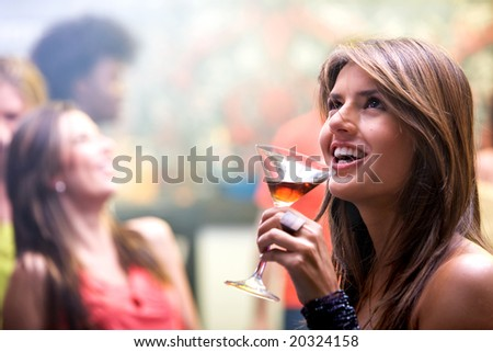 happy and smiling woman in a bar or a nightclub having a cocktail drink - stock photo