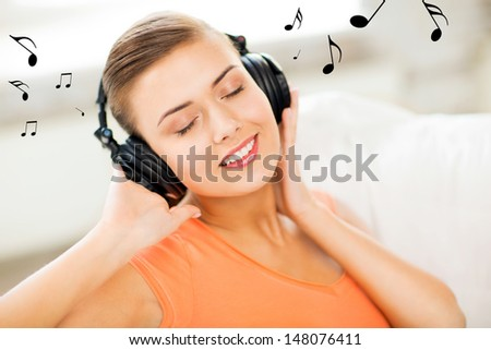 happy and smiling woman with headphones at home - stock photo