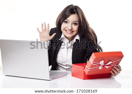 Happy and smiling young business woman at the desk with a laptop opens a box with a gift