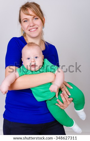 Happy and smiling Young mother and son, mom playing With Their Baby boy 4 month old on grey background. Concept happy family - stock photo