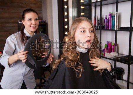 Happy and surprised client looking at mirror in salon - stock photo