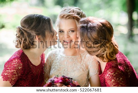 happy and young bride and her bridesmaids standing together