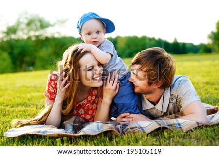 Happy and young family has a rest with a little son on nature in - stock photo