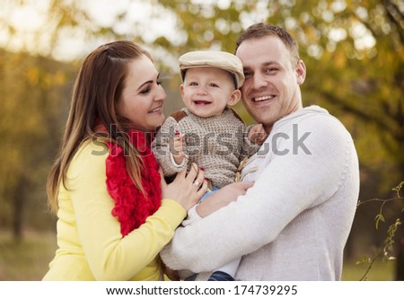 Happy and young family relaxing together in golden and colorful autum nature