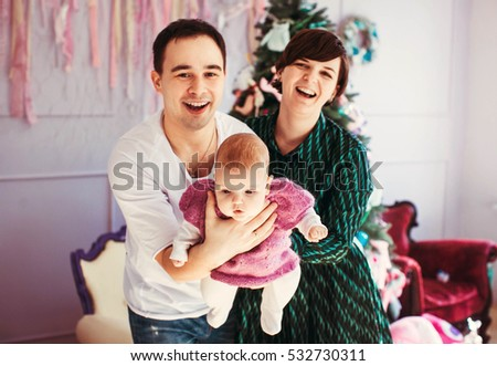 happy and young parents playing with their cute and small babygirl