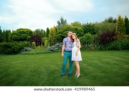 Happy and young pregnant couple in nature