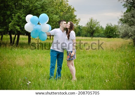 Happy and young pregnant couple outdoors - stock photo