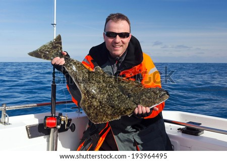Happy angler with halibut fish - stock photo