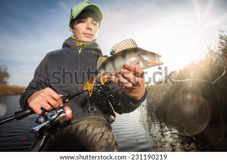 Happy angler with perch fishing trophy - stock photo