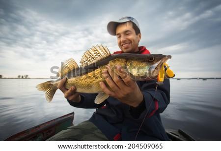 Happy angler with zander fishing trophy  - stock photo