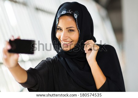 happy arabian woman taking self portrait using cell phone - stock photo