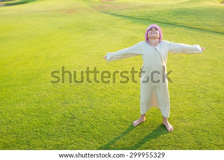 Happy Arabic cute boy on green meadow - stock photo