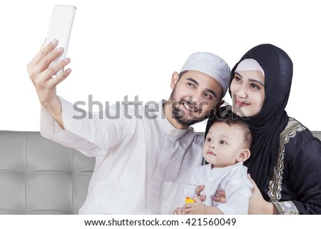 Happy Arabic family using a mobile phone to take selfie picture together while sitting on the sofa - stock photo