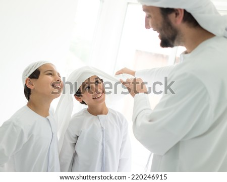 Happy Arabic father making headscarf to his son - stock photo