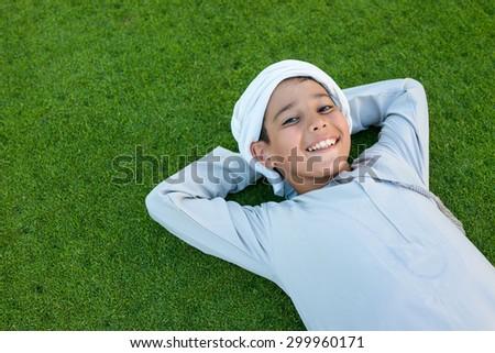 Happy Arabic kid on green grass - stock photo