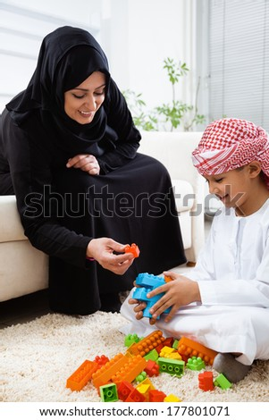 Happy Arabic mother and son together at home playing with toys.