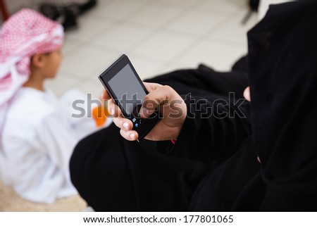 Happy Arabic mother using smart phone and her son together at home. - stock photo