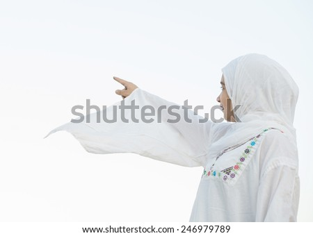 Happy Arabic Muslim Middle Eastern girl pointing at direction - stock photo